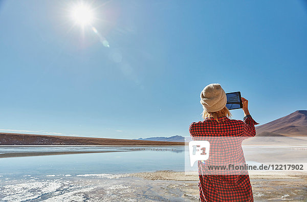 Frau fotografiert Landschaft  mit digitalem Tablett  Salar de Chalviri  Chalviri  Oruro  Bolivien  Südamerika