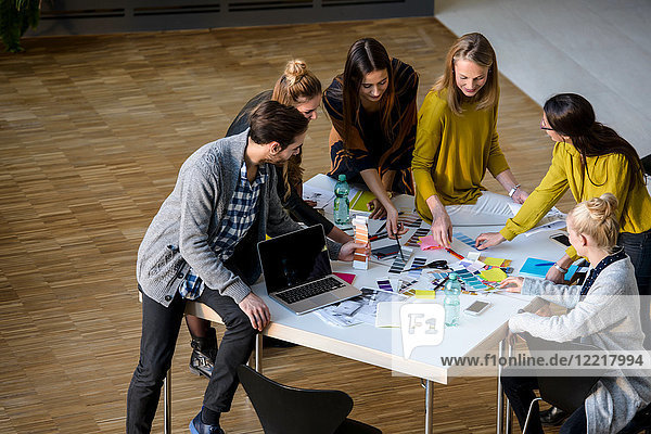 Team of male and female designers discussing colour swatches on design studio table
