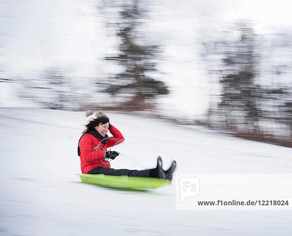 Schlitten fahrende Frau auf verschneitem Hügel