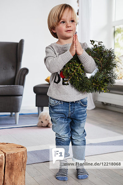 Young boy standing with hands together  holding wreath over arm