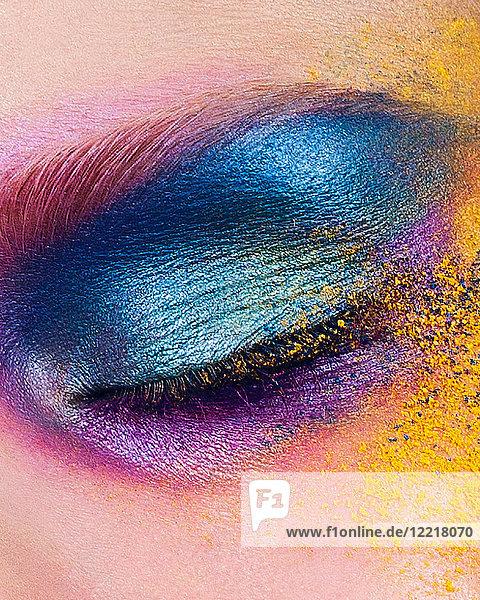 Studioaufnahme des Auges einer jungen Frau mit mehrfarbigem Puderlidschatten  Nahaufnahme
