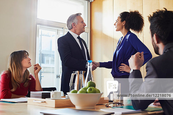 Businesswoman and man shaking hands at office meeting
