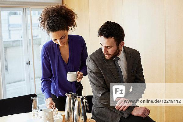 Geschäftsfrau und Mann machen während einer Bürobesprechung eine Kaffeepause