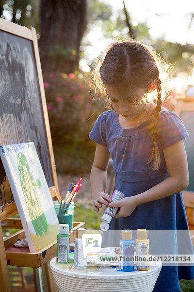Mädchen drückt im Garten Farbe auf die Palette