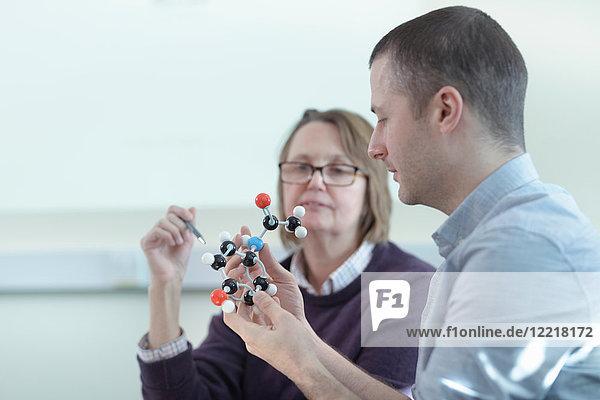 Scientists inspecting Ibuprofen model in meeting room