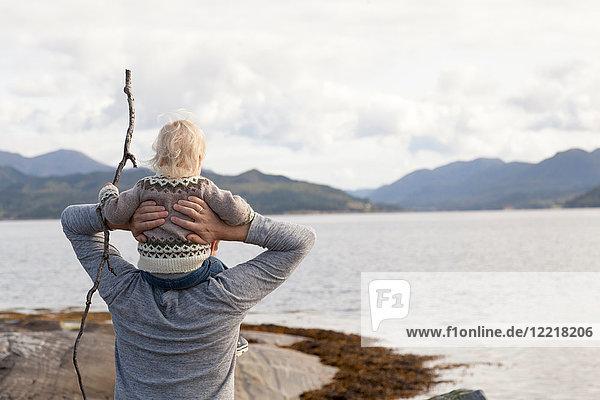Mann und Sohn schauen auf den Fjord  Aure  More og Romsdal  Norwegen