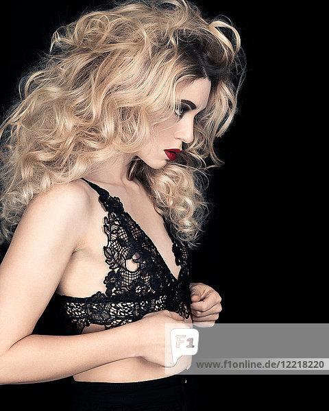 Studioporträt einer glamourösen jungen Frau in Spitzenbüstenhalter