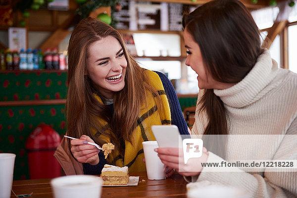 Junge Frauen lächeln über Textnachrichten auf Mobiltelefonen