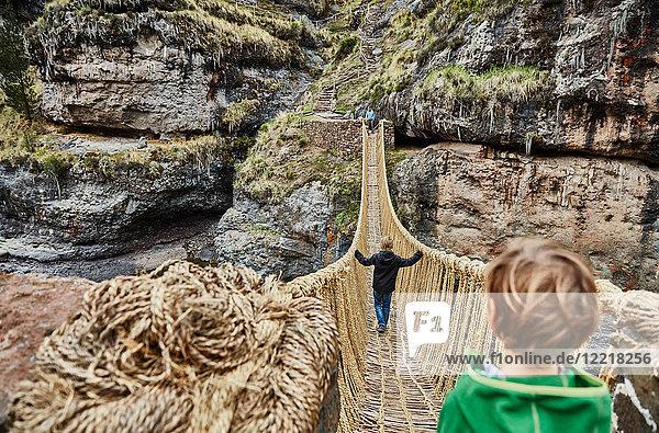 Über-Schulter-Ansicht von Junge  Bruder und Mutter beim Überqueren der Inka-Seilbrücke  Huinchiri  Cusco  Peru