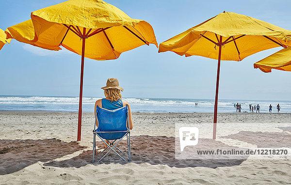 Rückansicht einer Touristin  die unter einem Sonnenschirm am Strand sitzt  Camana  Arequipa  Peru