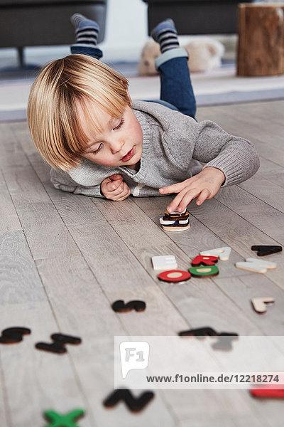 Auf dem Boden liegender Junge  der magnetische Briefe stapelt