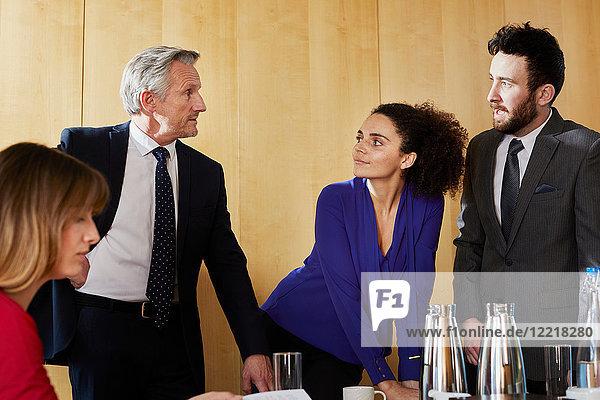 Geschäftsmänner und -frauen diskutieren bei Bürotreffen