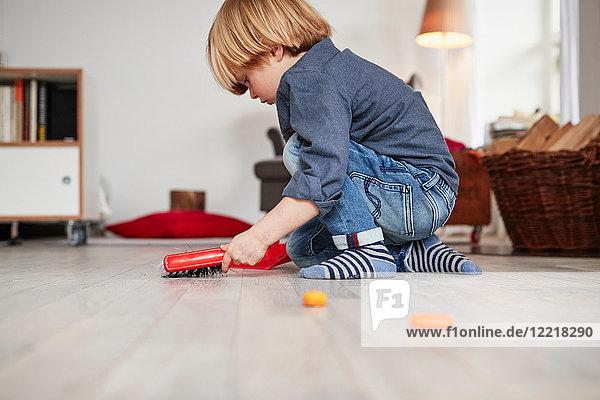 Kleiner Junge spielt mit Spielzeug-Kehrschaufel und Bürste