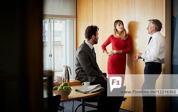Geschäftsfrau und Männer mit Bürobesprechung