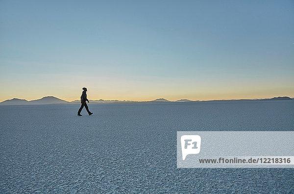 Frau geht über die Salinen  Salar de Uyuni  Uyuni  Oruro  Bolivien  Südamerika