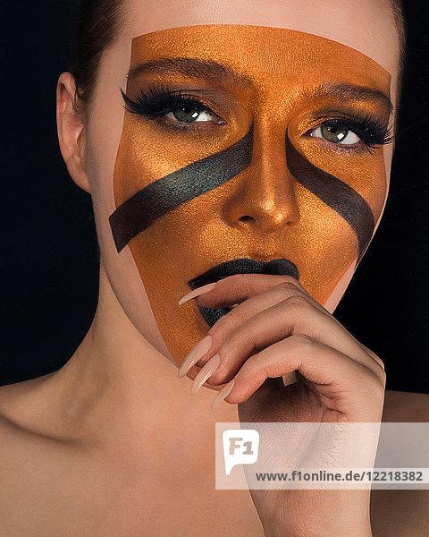 Studioporträt einer jungen Frau mit nackten Schultern  Bronze im Gesicht und schwarzem Lippenstift  Nahaufnahme