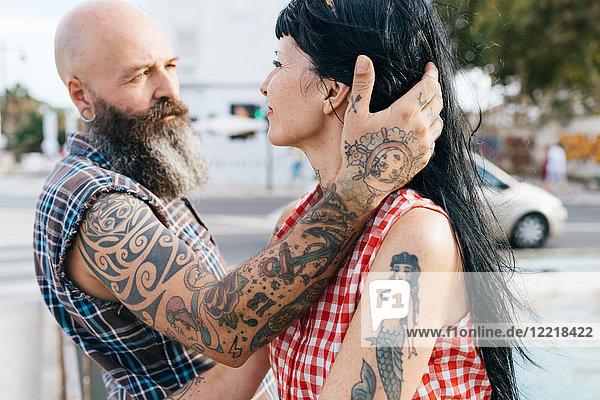 Erwachsener tätowierter Hipster-Mann mit Hand im Haar der Freundin