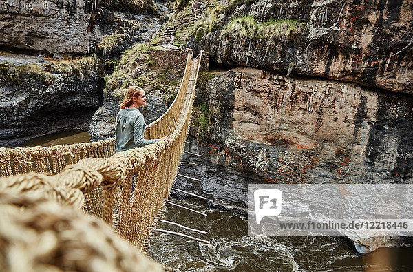 Touristin  die von der Inka-Seilbrücke hinausblickt  Huinchiri  Cusco  Peru