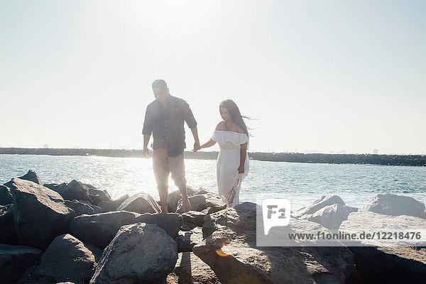 Couple walking on coastal rocks  holding hands  Seal Beach  California  USA
