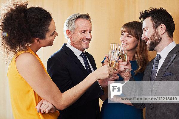 Geschäftsteam stößt bei Bürofeier mit Champagner an