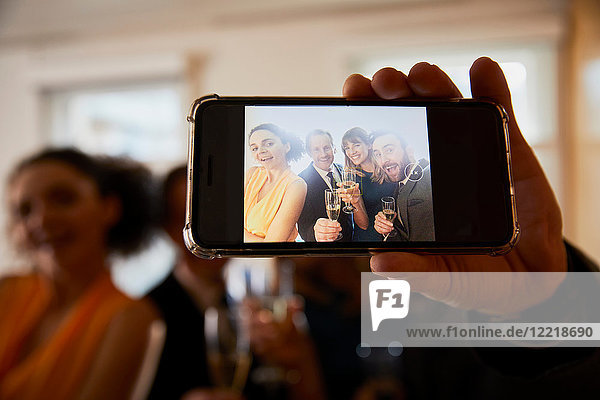Business team raising champagne toast at office celebration  smartphone selfie close up