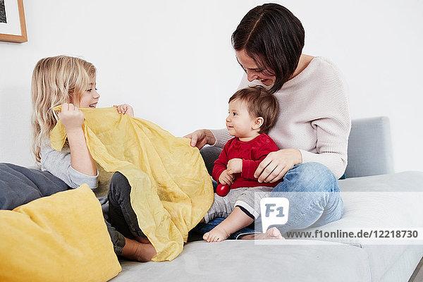 Familie sitzt auf dem Sofa  junges Mädchen spielt mit der kleinen Schwester Kuckuck spielen