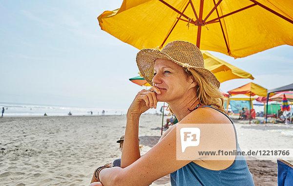 Weibliche Touristin sitzt unter einem Sonnenschirm  Camana  Arequipa  Peru