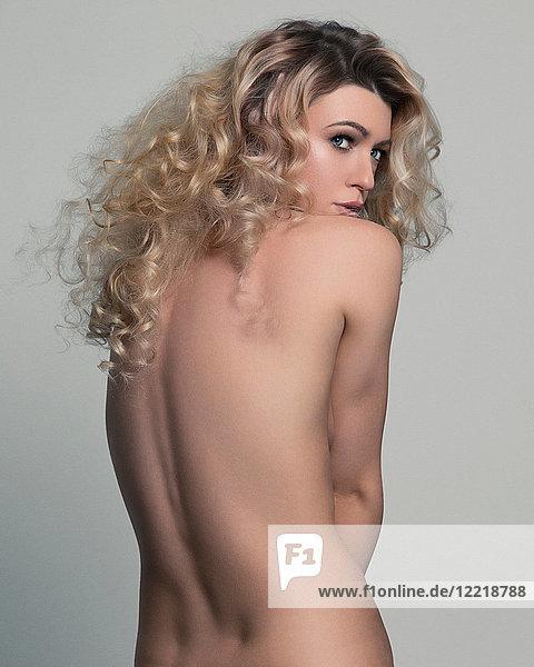 Nacktes Studioporträt einer jungen Frau  die über ihre Schulter schaut