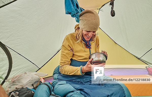 Frau sitzt im Zelt und isst Essen aus Schüssel  Ventilla  La Paz  Bolivien  Südamerika