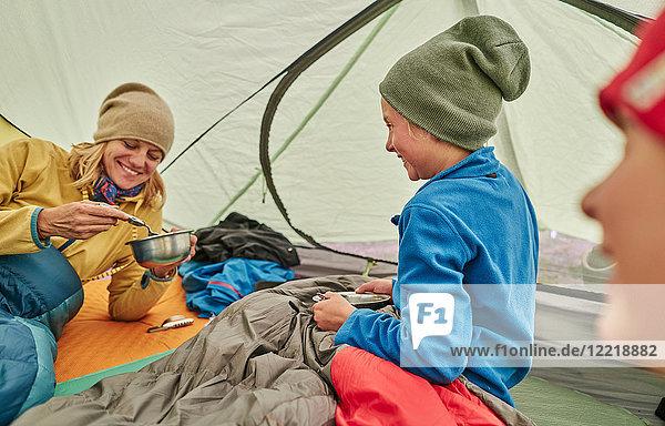 Mutter und Söhne im Zelt  essen Essen aus Schüsseln  Ventilla  La Paz  Bolivien  Südamerika