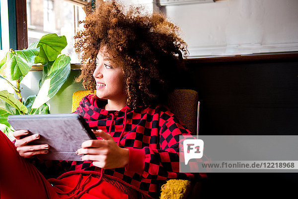 Young woman sitting indoors  using digital tablet