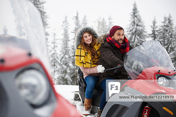 Young couple riding snowmobile in winter