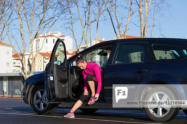 Young woman in car tying shoelace on training shoe  stretching legs