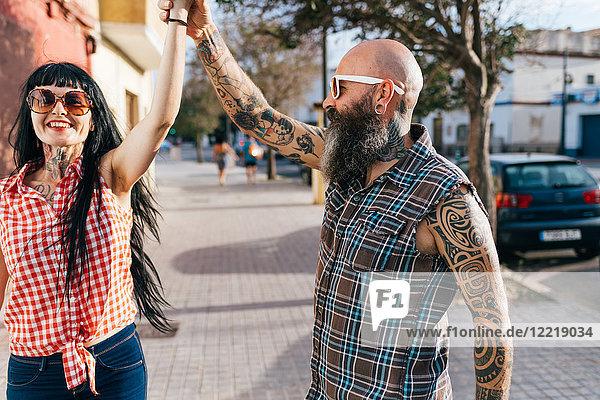 Ausgewachsenes Hipster-Paar tanzt auf dem Bürgersteig