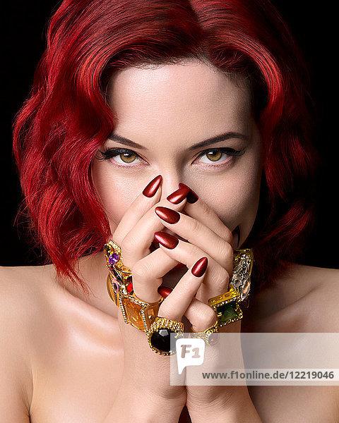 Porträt einer jungen Frau mit roten Haaren  die Hände bedecken das Gesicht und tragen Ringe an allen Fingern
