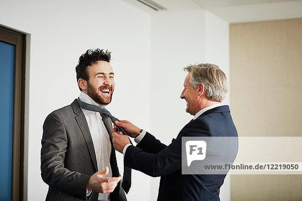 Senior businessman fastening colleague's tie in office