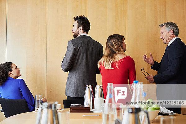Geschäftsfrauen und -männer machen eine Pause während einer Bürositzung