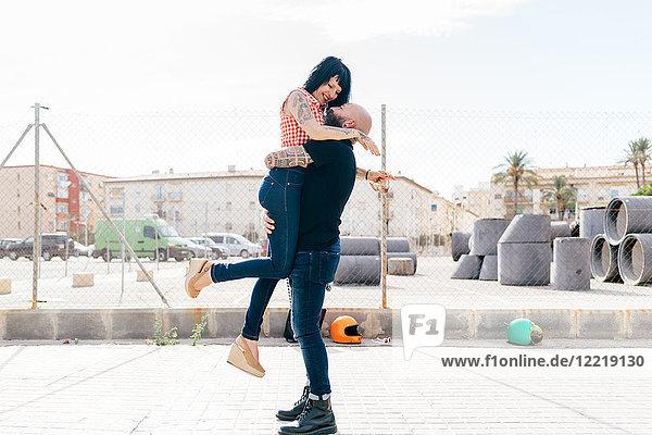 Erwachsener Hipster-Mann hebt und umarmt Freundin in der Stadt