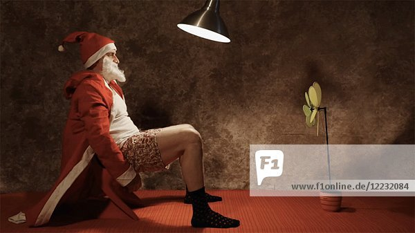 Santa Claus Sitting in Chair  Open Robe  Boxer Shorts  Shadow from Swinging Hanging Lamp Moves Across Wall