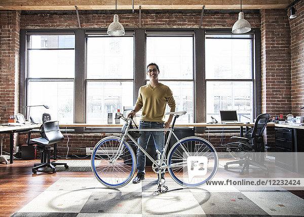 Ein spanischer Mann an seinem Büroarbeitsplatz mit einem Fahrrad.