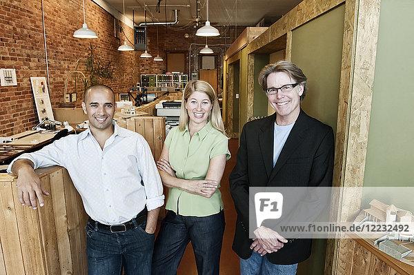 Porträt eines multiethnischen Teams von drei Architekten in einem kleinen Büro.