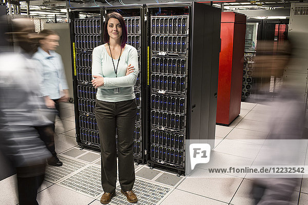 Caucasian woman technician standing in an aisle of a large computer server farm.