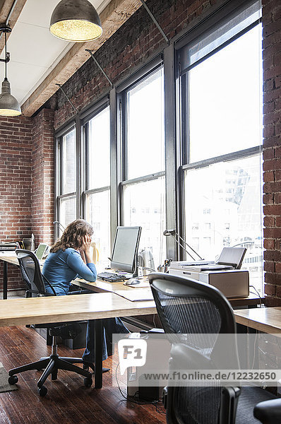 Caucasian woman at office workstation near a large bank of windows.