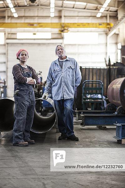 Schwarze Frau und kaukasische Arbeiter in einer Blechfabrik.