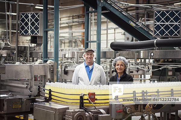 Porträt eines kaukasischen männlichen und eines afroamerikanischen weiblichen Mitarbeiterteams  die Kopfnetze tragen und neben einem Förderband für Wasser mit Zitronenaroma in einer Abfüllanlage stehen.