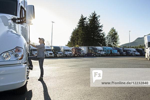 Kaukasische Lkw-Fahrerin steigt in ihren Lkw  der auf einem Parkplatz an einer Raststätte geparkt ist.