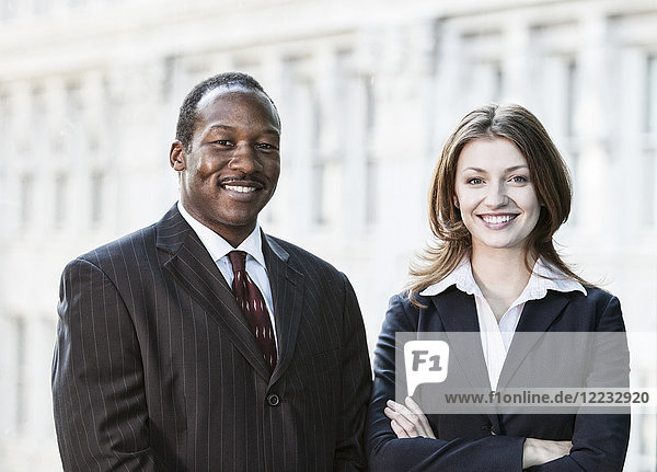 Black business man and Caucasian business woman together in front of an older office building.