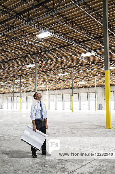 Caucasian man going over plans for new warehouse interior in front of loading dock doors.