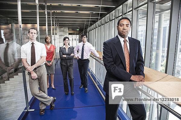 Ein Team von Männern und Frauen  ein ethnisch vielfältiges Team von Geschäftsleuten in der Lobby eines großen Bürogebäudes.