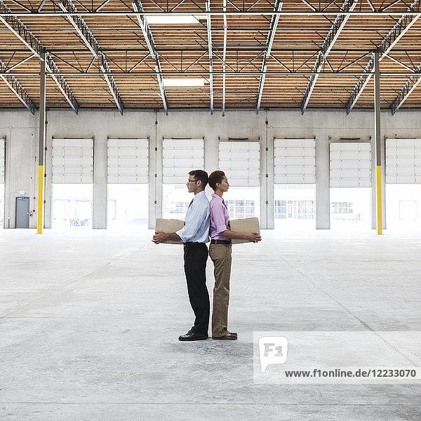 Kaukasischer Mann und schwarze Frau halten Pappkartons in der Mitte eines leeren Lagerhauses.